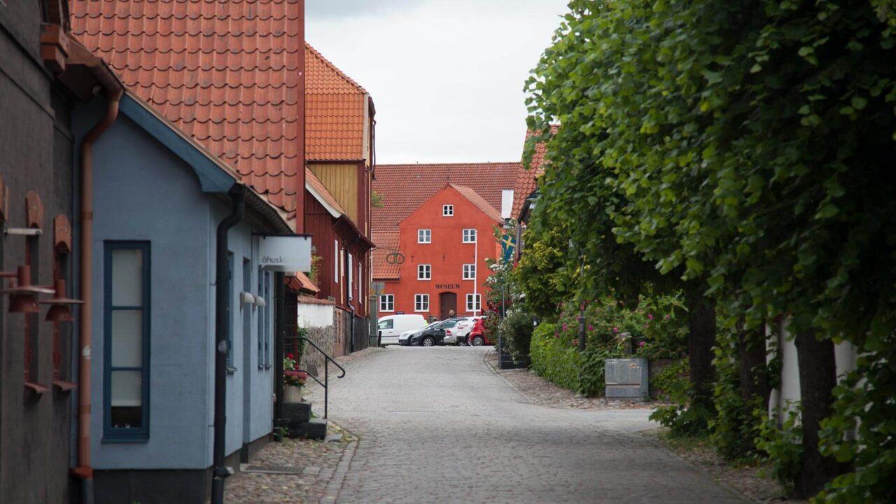 I bakgrunden syns ett rött putsat hus, Åhus museum