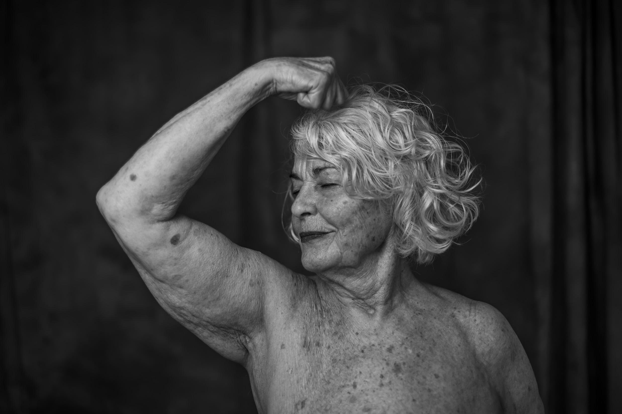 Svartvit bild av äldre kvinna i halvfigur som spänner armen som för att visa armmuskler.