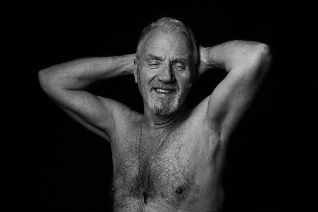 Svartvit halvfigursbild på en äldre man med bart bröst.