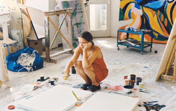 En ung kvinna sitter på knä i en ateljé. Framför henne på golvet ligger två vita taveldukar.