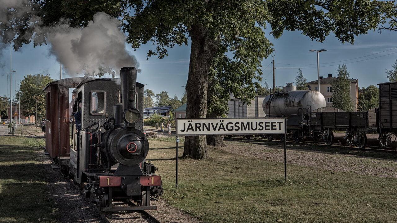 Ett litet ånglok fram för en skylt med texten Järnvägsmuseet.