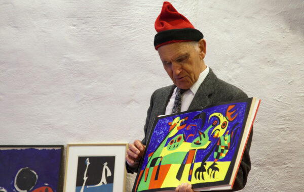 Nils Tryding håller upp en konstaffisch av Joan Miró