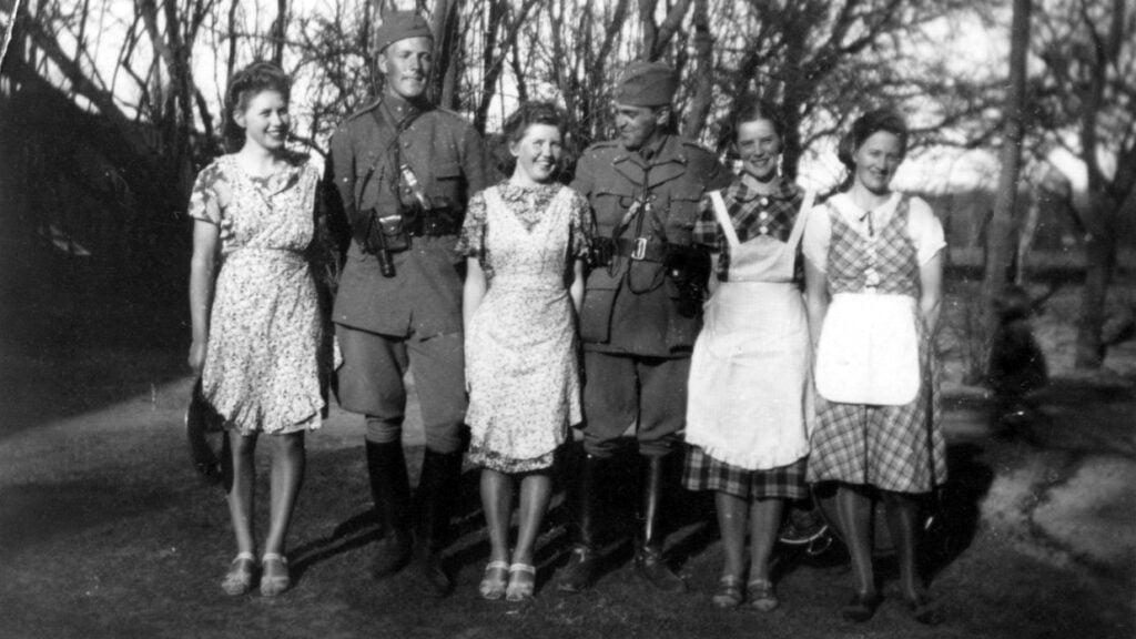 Två militärer på rad med fyra kvinnor iförda förkläden utomhus.