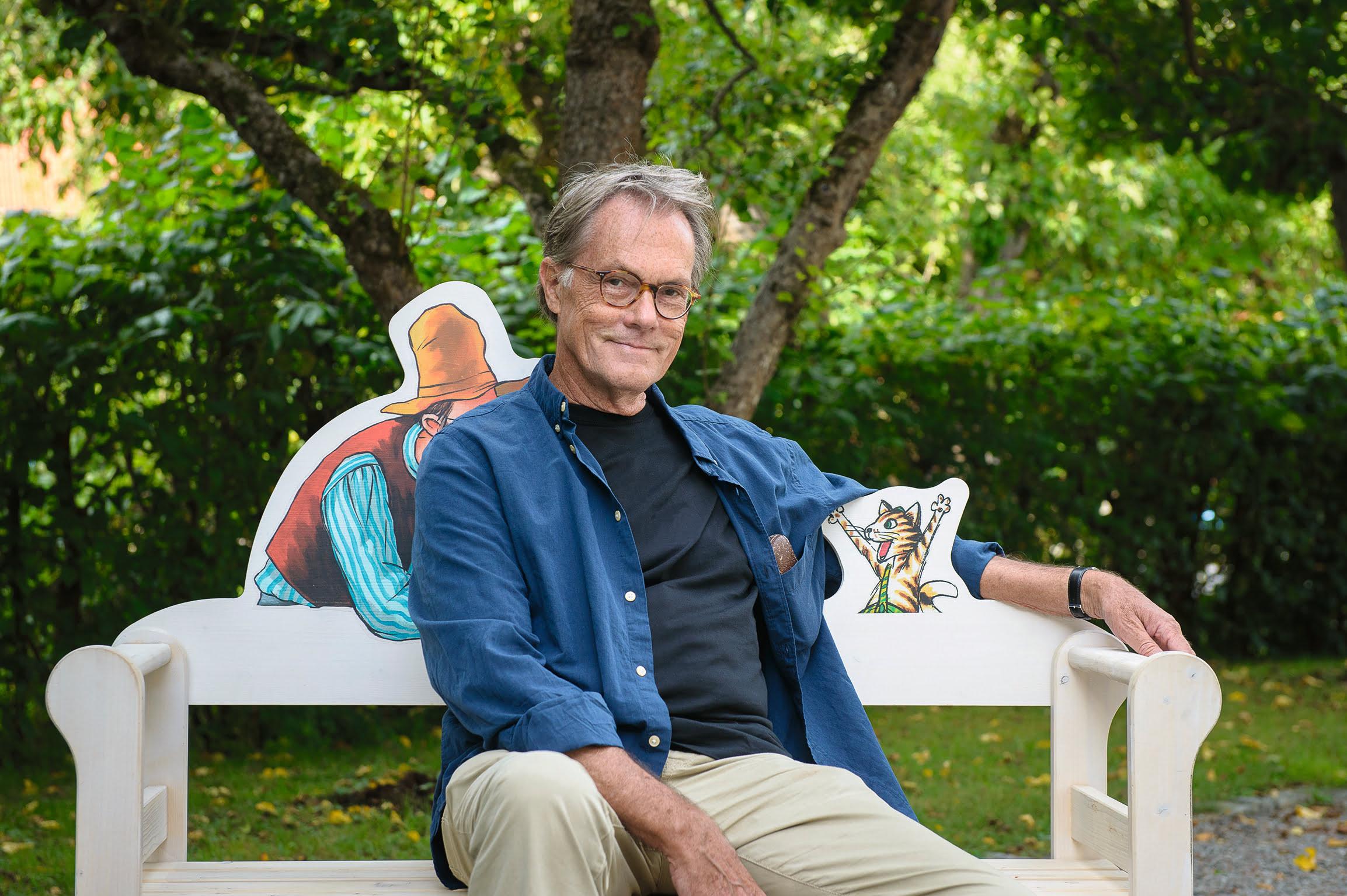 Man sitter på en träsoffa i en trädgård med två tecknade figurer på soffans ryggstöd.
