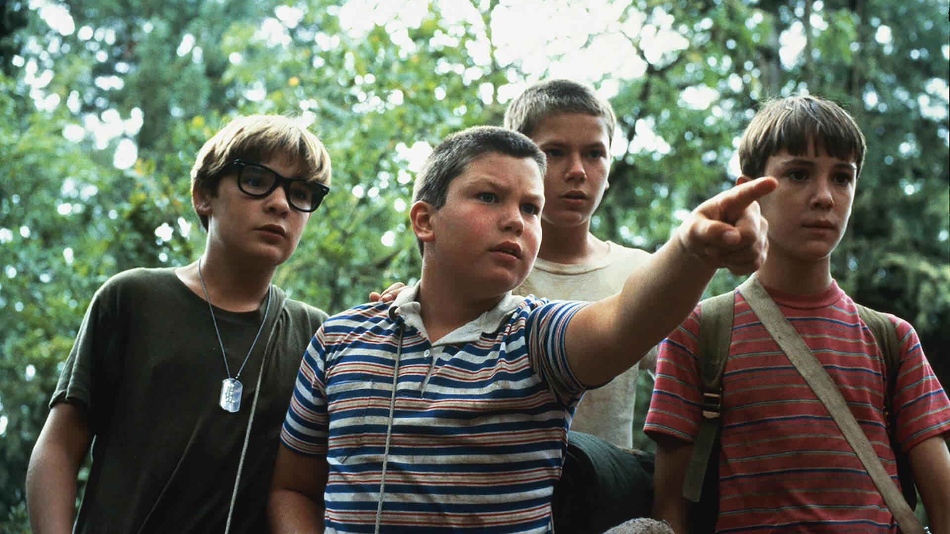 Fyra unga pojkar som tittar mot bildens högra hörn. En pojke pekar på något utanför bilden.